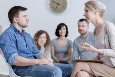 upset man sitting in group therapy