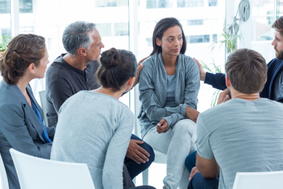 group of people consulting and giving comfort to a woman