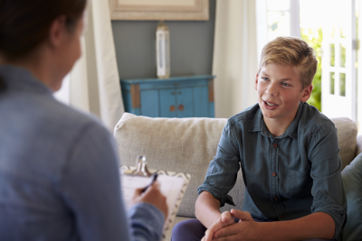 teenage boy with problem talking to the counselor